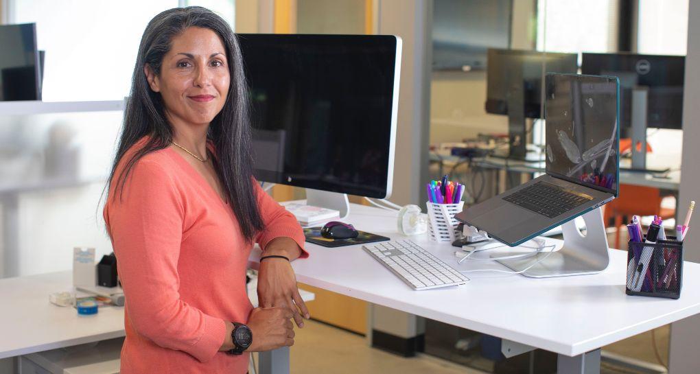 Kvinde der står foran computere på hæve sænkebord